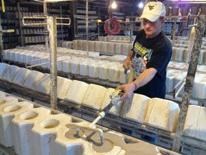 Small business, big impact: a worker pours liquid ceramic into molds