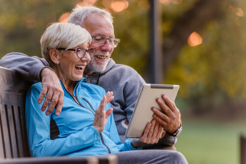 Retired couple laugh together viewing Mylio photos on Valentine's Day